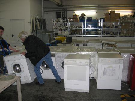 Reparatur der Elektrogroßgeräte - Bild zeigt zwei Männer, die eine Waschmaschine transportieren